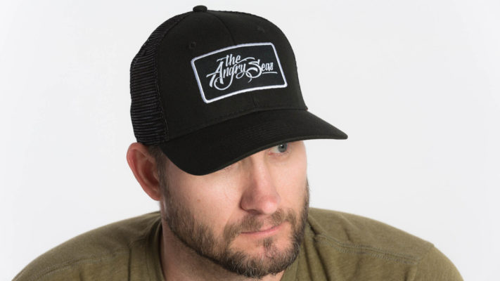 "Product: ""Ture Script"" Snapback Hat // Description: Semi-Curved Bill mesh snapback hat with woven label appliqué // Color: Black on Black // Brand: The Angry Seas Clothing"