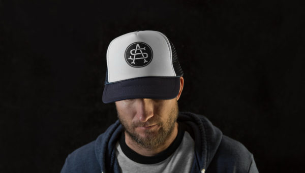 "Product: ""Monogram"" Trucker Hat // Description: Foam Trucker mesh snapback hat with screen-printed logo // Color: Blue // Brand: The Angry Seas Clothing"